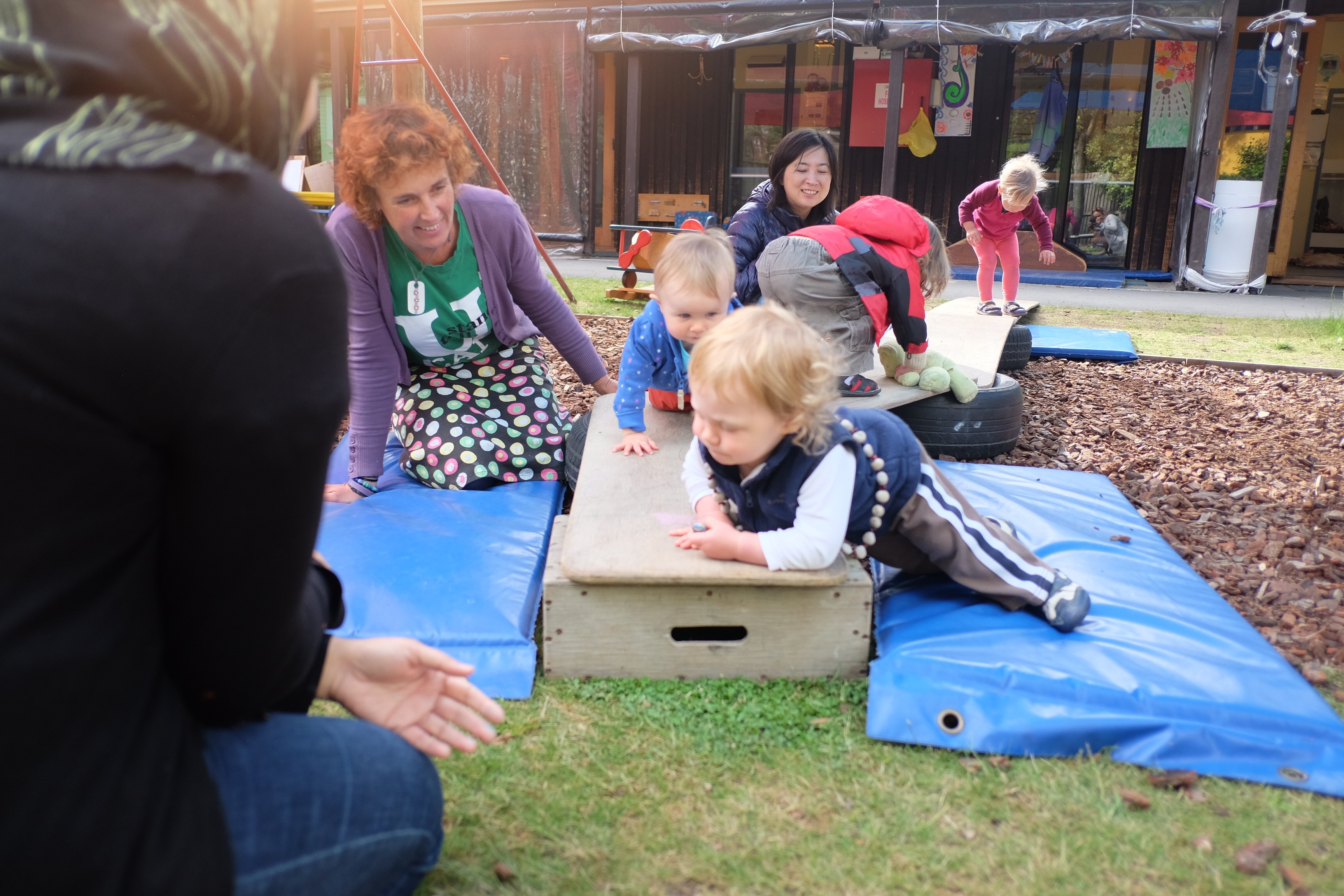 Childcare centre children playing with teachers on mat outside